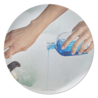 Close-up of a woman's hand pouring aromatherapy plate