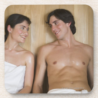 Close-up of a young couple sitting in a sauna coaster