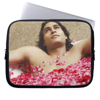 Close-up of a young man lying in a bathtub laptop sleeve