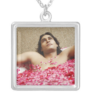 Close-up of a young man lying in a bathtub silver plated necklace