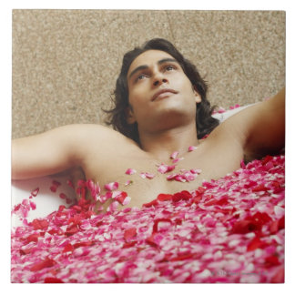 Close-up of a young man lying in a bathtub tile
