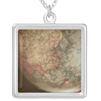 Close-up of antique globe silver plated necklace