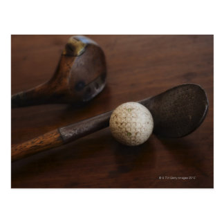 Close up of antique golf clubs and golf ball post cards