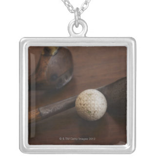 Close up of antique golf clubs and golf ball silver plated necklace
