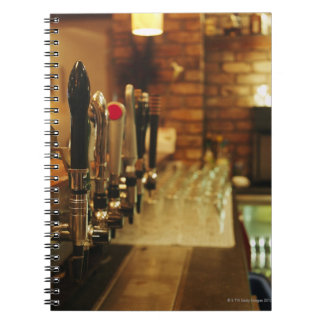 Close-up of beer taps in bar 2 spiral note book