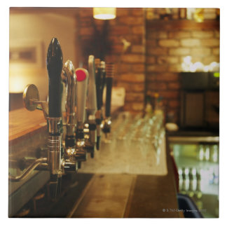 Close-up of beer taps in bar 2 tile
