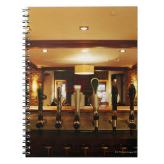 Close-up of beer taps in bar note book