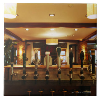 Close-up of beer taps in bar tile