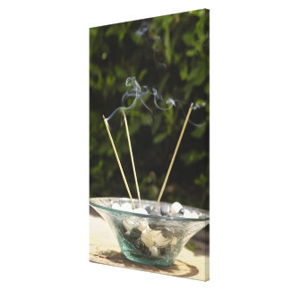 Close-up of burning incense sticks with pebbles canvas print