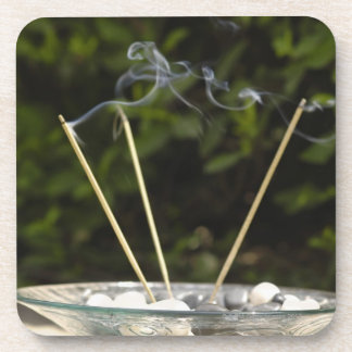 Close-up of burning incense sticks with pebbles coaster