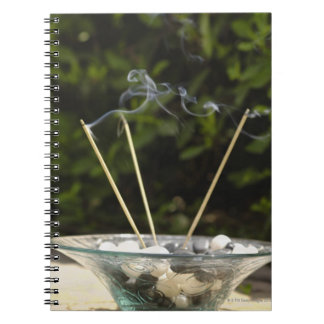 Close-up of burning incense sticks with pebbles notebook