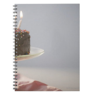 Close up of chocolate birthday cake with candles notebook