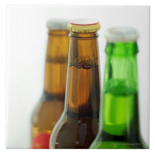 close-up of coloured bottles of beer tile