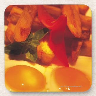 close-up of fried eggs with french fries drink coaster