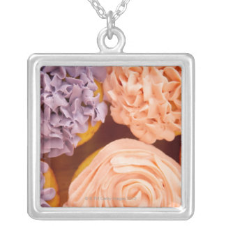 Close-up of frosted cupcakes silver plated necklace