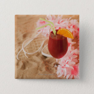 Close up of frozen drink and lei on sand 15 cm square badge