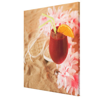 Close up of frozen drink and lei on sand canvas print