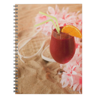 Close up of frozen drink and lei on sand notebook