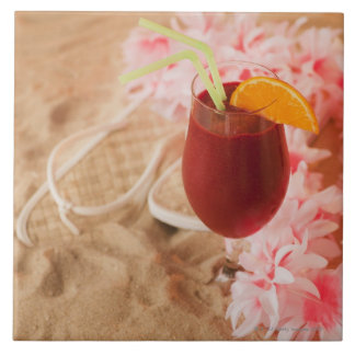 Close up of frozen drink and lei on sand tile