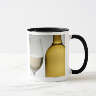Close up of glass of white wine and wine bottle mug