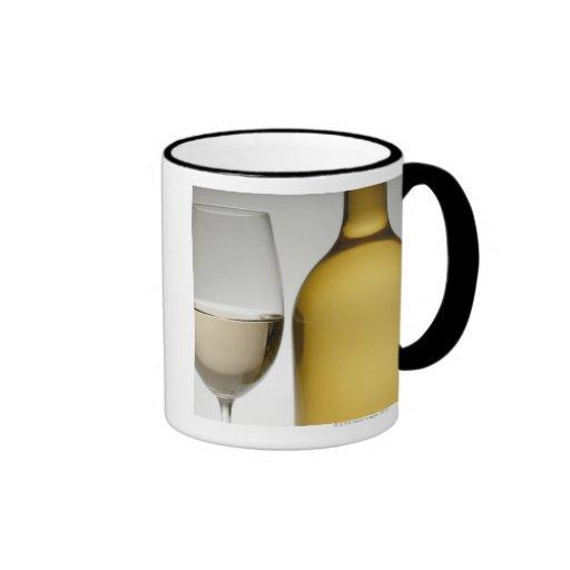Close up of glass of white wine and wine bottle mug