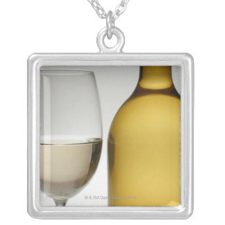 Close up of glass of white wine and wine bottle silver plated necklace