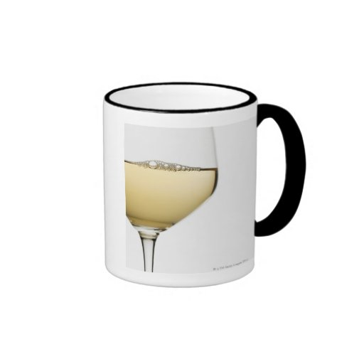 Close up of glass of white wine on white coffee mugs