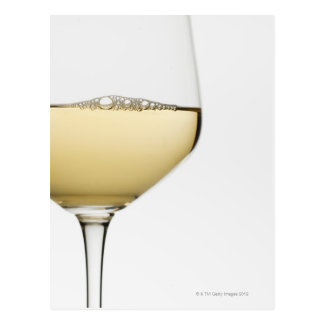 Close up of glass of white wine on white postcard