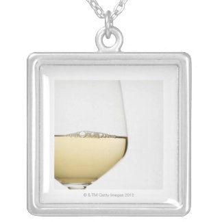 Close up of glass of white wine on white silver plated necklace