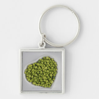 Close-up of green pebbles in a heart shape bowl key ring