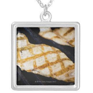 Close-up of grilled chicken breasts silver plated necklace