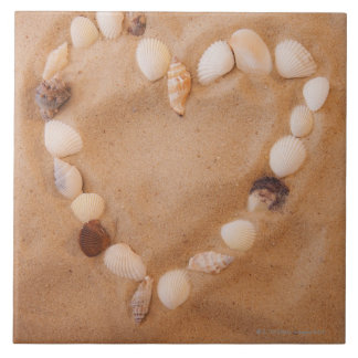Close up of heart shape made of shells on sand tile