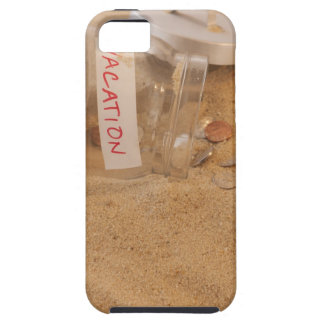Close up of jar with coins spilled on sand iPhone 5 covers