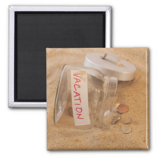 Close up of jar with coins spilled on sand square magnet