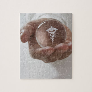Close up of man holding clear ball with Caduceus Jigsaw Puzzle