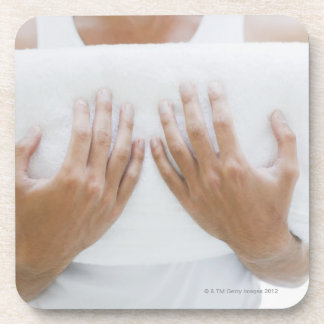 Close up of man holding towels coaster