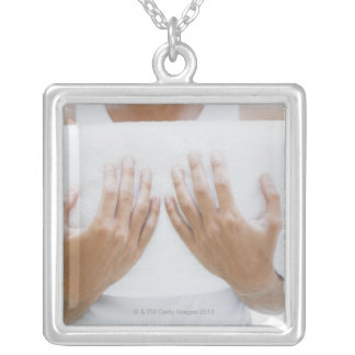 Close up of man holding towels silver plated necklace