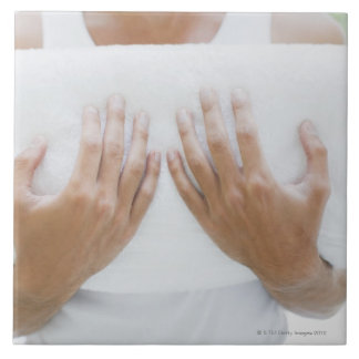 Close up of man holding towels tile