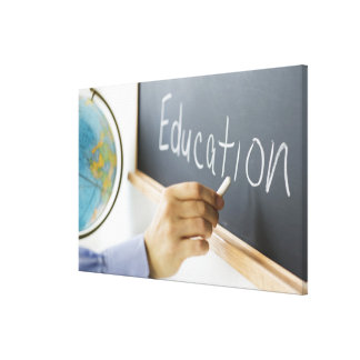 Close-up of man's hand writing ''education'' on canvas print