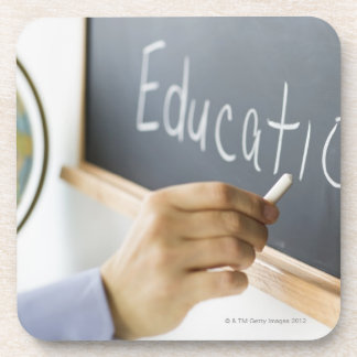 Close-up of man's hand writing ''education'' on coaster