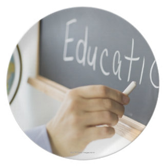 Close-up of man's hand writing ''education'' on plate
