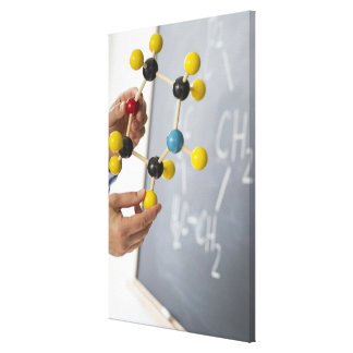 Close-up of man's hands holding molecule model, canvas print