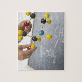 Close-up of man's hands holding molecule model, jigsaw puzzle