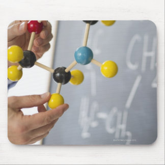 Close-up of man's hands holding molecule model, mouse mat