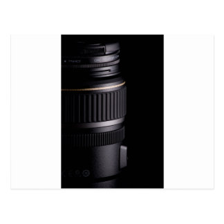 Close up of modern camera lens on black background postcard