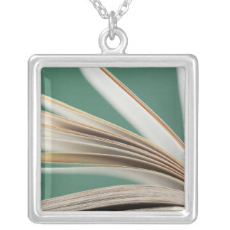 Close-up of open book, studio shot silver plated necklace