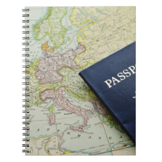 Close-up of passport lying on European map Notebook