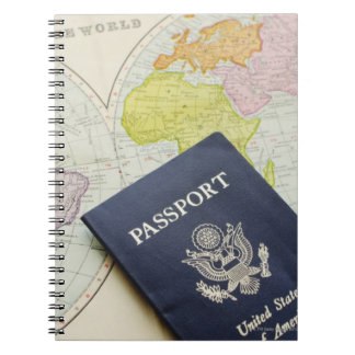 Close-up of passport lying on map notebooks