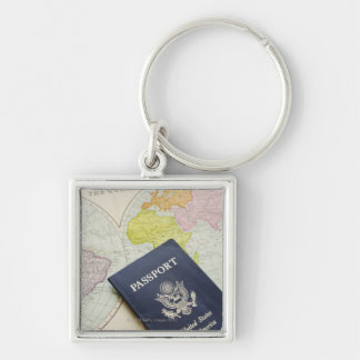 Close-up of passport lying on map Silver-Colored square key ring
