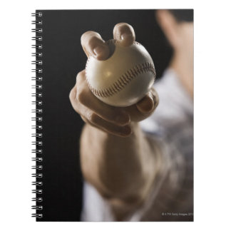 Close up of pitcher holding baseball note book